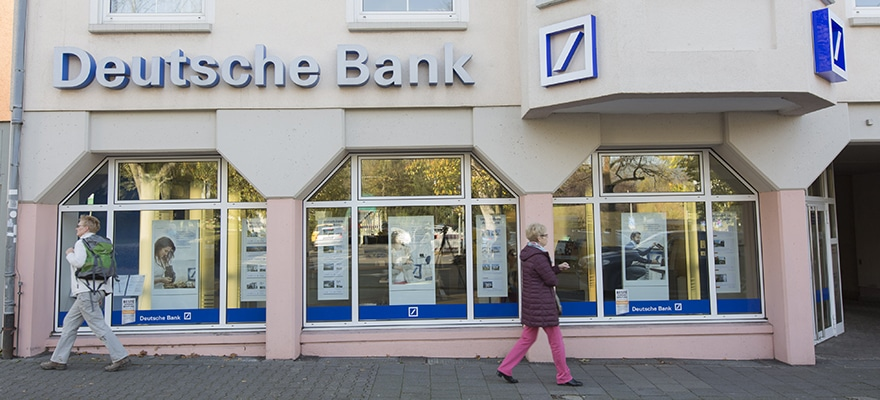 Pedestrians pass a Deutsche Bank AG bank branch in Koenigstein, Germany, on Friday, Oct. 24, 2014. The cost for banks to settle probes into allegations traders rigged foreign-exchange benchmarks could hit as much as $41 billion, Citigroup Inc. analysts said. Photographer: Martin Leissl/Bloomberg