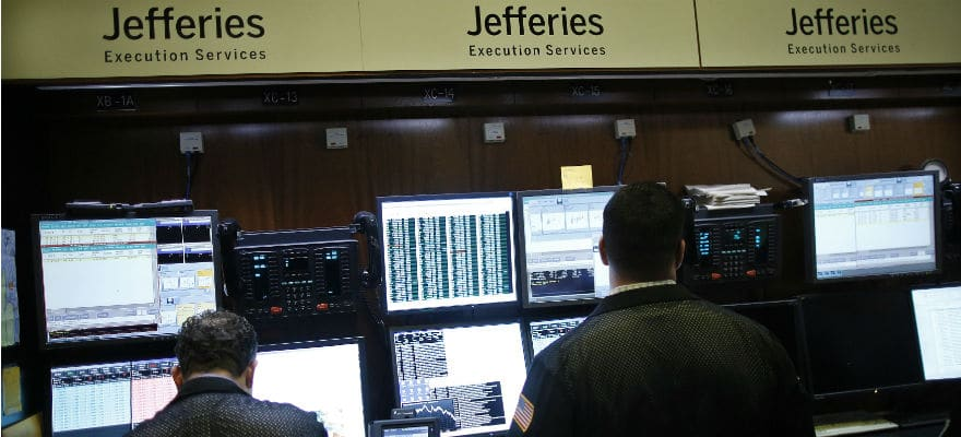 Jefferies Group logo above a group of people on their computers