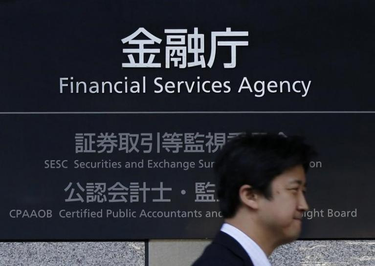 A man walks past a sign of Japan's Financial Services Agency (FSA) at its headquarters in Tokyo November 5, 2013. REUTERS/Toru Hanai