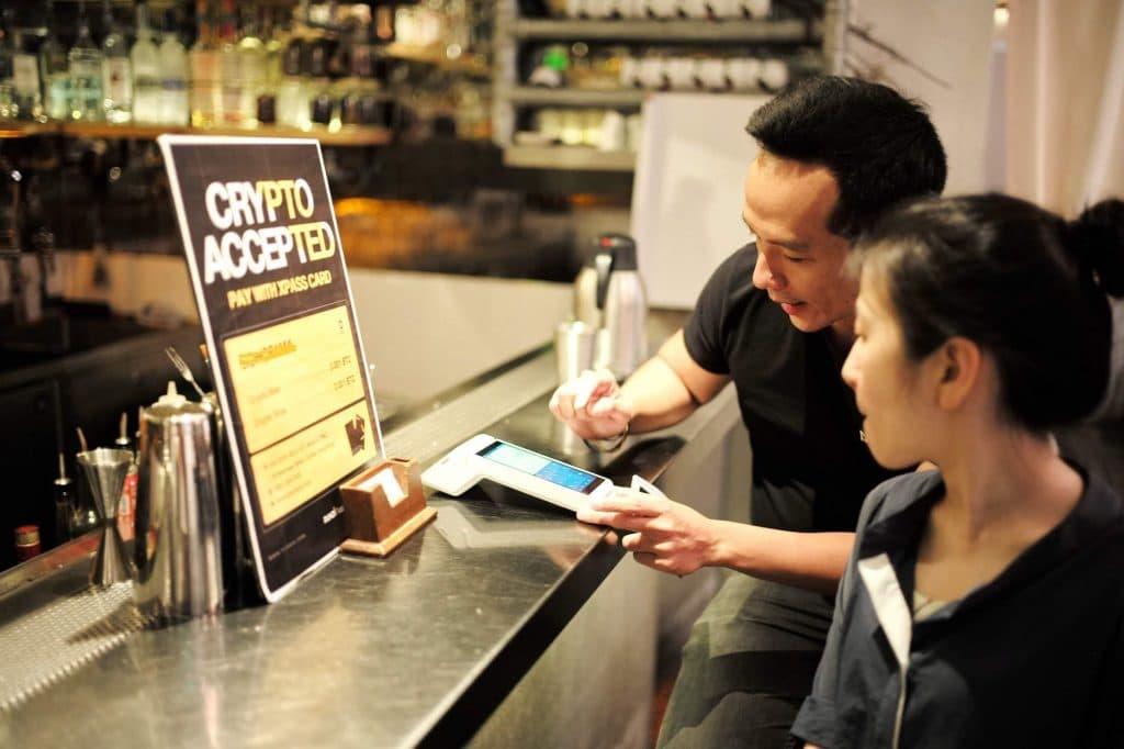 Zac Cheah, CEO and Co-founder of Pundi X, shows a merchants how his company's payment system works